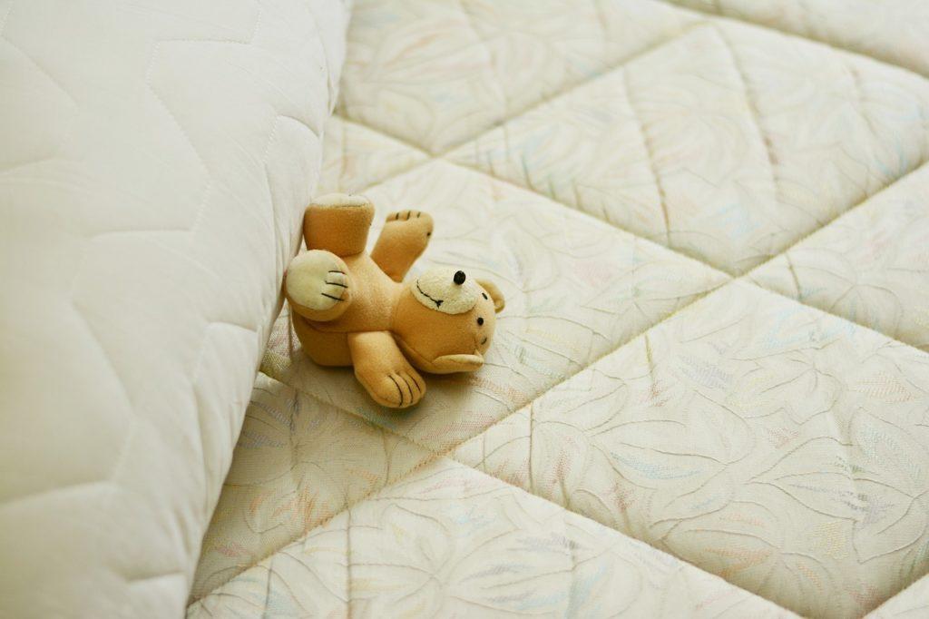 ベッドで眠るくまの画像